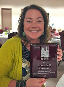 """Brandy Moe shows the plaque that reads """"In Appreciation of Outstanding Community Service"""" for her community service to Ruby Hill."""