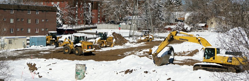 Photo of construction vehicles in the snow, clearing an area where the Ruby Hill Residences will be built