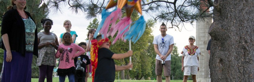 A child swings at a piñata at the annual neighborhood picnic.