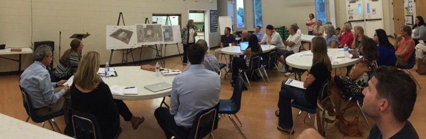Panoramic view of neighbors attending the Ruby Hill-Godsman neighborhood association meeting while a presenter points at some concepts on an easel.