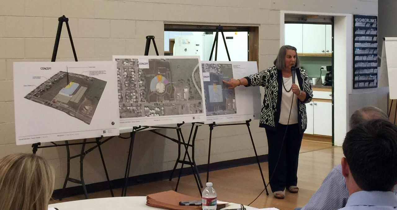 A woman points at three easels showing concepts for a Colorado Public Radio office building near Ruby Hill Park