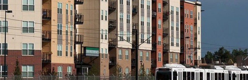 Photo showing a light rail and apartment building near I-25 and Broadway.